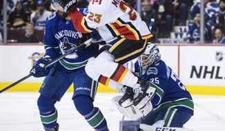 Calgary Flames' Sean Monahan (23) jumps in front of Vancouver Canucks goalie Jacob Markstrom, of Sweden, as he makes a glove save while Erik Gudbranson, back left, defends during the first period of an NHL hockey game Saturday, Feb. 9, 2019, in Vancouver, British Columbia. (Darryl Dyck/The Canadian Press via AP)