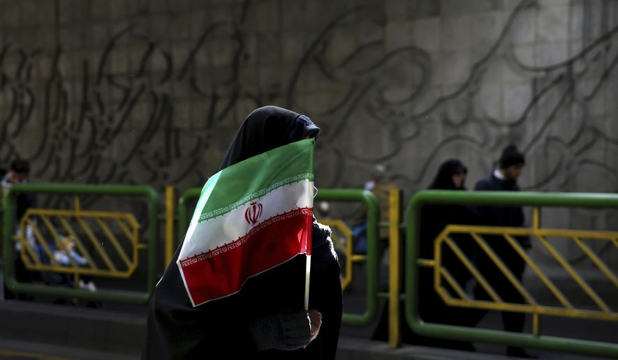 In this Feb. 11, 2016, file photograph, an Iranian woman holds the national flag during a rally commemorating the 37th anniversary of the Islamic revolution, in Tehran, Iran. (AP Photo/Ebrahim Noroozi, File)