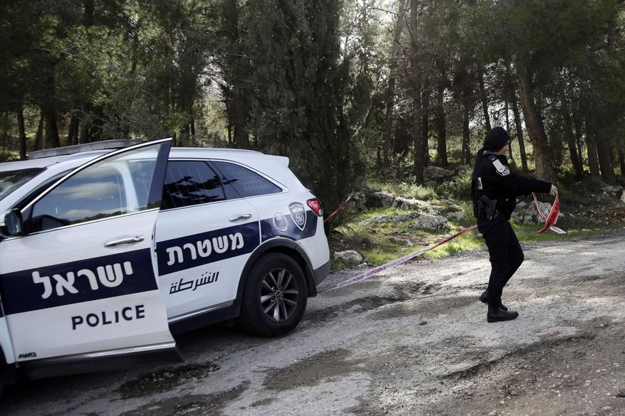 FILE - In this Friday, Feb. 8, 2019 file photo, an Israeli police officer blocks the area where the body of an Israeli woman was found in Jerusalem. Israel's internal security agency said in a statement Sunday Feb. 10, 2019, the murder of a 19-year-old Israeli woman by a Palestinian suspect near Jerusalem last week was politically motivated.(AP Photo/Mahmoud Illean)