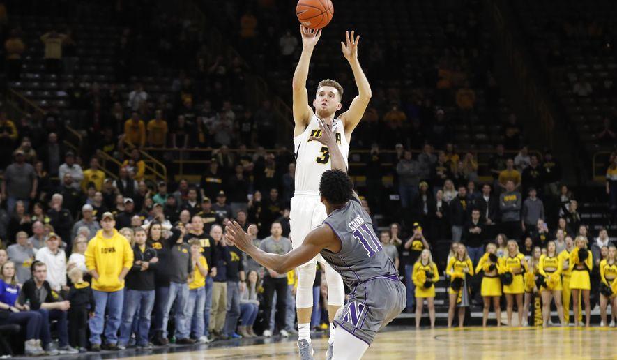 Iowa guard Jordan Bohannon (3) shoots a three point basket over Northwestern guard Anthony Gaines (11) at the end of an NCAA college basketball game, Sunday, Feb. 10, 2019, in Iowa City, Iowa. Iowa won 80-79. (AP Photo/Charlie Neibergall)