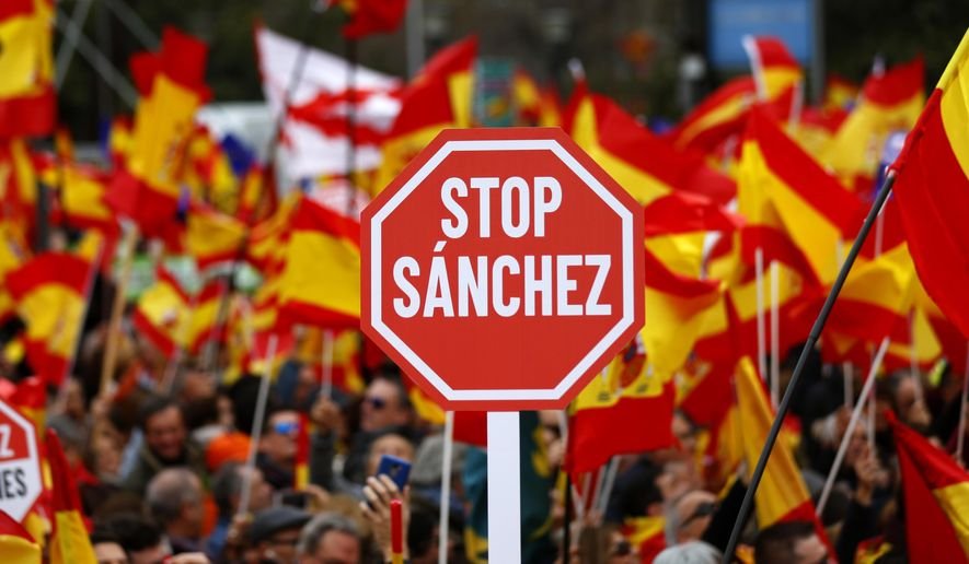 Demonstrators hold banners and Spanish flags during a protest in Madrid, Spain, on Sunday, Feb.10, 2019. Thousands of Spaniards in Madrid are joining a rally called by right-wing political parties to demand that Socialist Prime Minister Pedro Sanchez step down. (AP Photo/Andrea Comas)