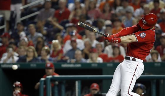 FILE - In this June 8, 2018, file photo, Washington Nationals' Bryce Harper hits a two-RBI double during the fifth inning of a baseball game against the San Francisco Giants at Nationals Park in Washington. Harper, Manny Machado, Craig Kimbrel and Dallas Keuchel will not be around when the bat and ball bags are opened at spring training throughout Florida and Arizona this week. They are among the dozens of free agents still looking for jobs. (AP Photo/Alex Brandon, File) **FILE**