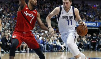 Portland Trail Blazers' Rodney Hood (5) defends as Dallas Mavericks forward Luka Doncic (77) drives to the basket for a shot in the first half of an NBA basketball game in Dallas, Sunday, Feb. 10, 2019. (AP Photo/Tony Gutierrez)