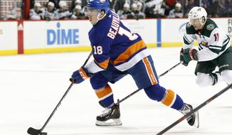 New York Islanders left wing Anthony Beauvillier (18) looks for a shot on goal with Minnesota Wild left wing Zach Parise (11) in pursuit in the second period of an NHL hockey game, Sunday, Feb. 10, 2019, in New York. (AP Photo/Kathy Willens)