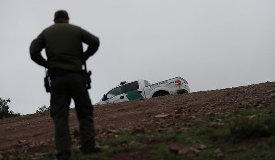 Border Patrol agent Vincent Pirro looks on near where a border wall ends that separates the cities of Tijuana, Mexico, and San Diego, Tuesday, Feb. 5, 2019, in San Diego. President Donald Trump is expected to speak about funding for a wall along the U.S.-Mexico border during his State of the Union address Tuesday. (AP Photo/Gregory Bull)