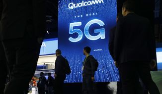 In this Jan. 9, 2019, file photo a sign advertises 5G at the Qualcomm booth at CES International in Las Vegas. 5G is a new technical standard for wireless networks that promises faster speeds; less lag, or latency, when connecting to the network; and the ability to connect many devices to the internet without bogging it down. (AP Photo/John Locher, File)