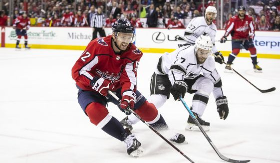 Washington Capitals center Evgeny Kuznetsov (92), of Russia, defends the puck past Los Angeles Kings defenseman Oscar Fantenberg (7), of Sweden, during the second period of an NHL hockey game against the Los Angeles Kings, Monday, Feb. 11, 2019, in Washington. (AP Photo/Al Drago)