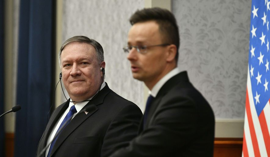 Hungary's Minister of Foreign Affairs and Trade Peter Szijjarto, right, talks as U.S. Secretary of State Mike Pompeo listens, during a joint press conference after their meeting in Budapest, Hungary, Monday, Feb. 11, 2019. Pompeo is in Budapest on the first leg of a five-nation European tour during which he said he would raise American concerns about China and Russia's growing influence in Central Europe. (Zsolt Szigetvary/MTI via AP)