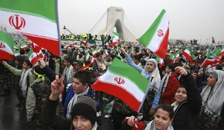 Children wave Iranian flags during a ceremony celebrating the 40th anniversary of the Islamic Revolution, at the Azadi, Freedom, Square in Tehran, Iran, Monday, Feb. 11, 2019. Hundreds of thousands of people poured out onto the streets of Tehran and other cities and towns across Iran, marking the date 40 years ago that is considered victory day in the country's 1979 Islamic Revolution. (AP Photo/Vahid Salemi)