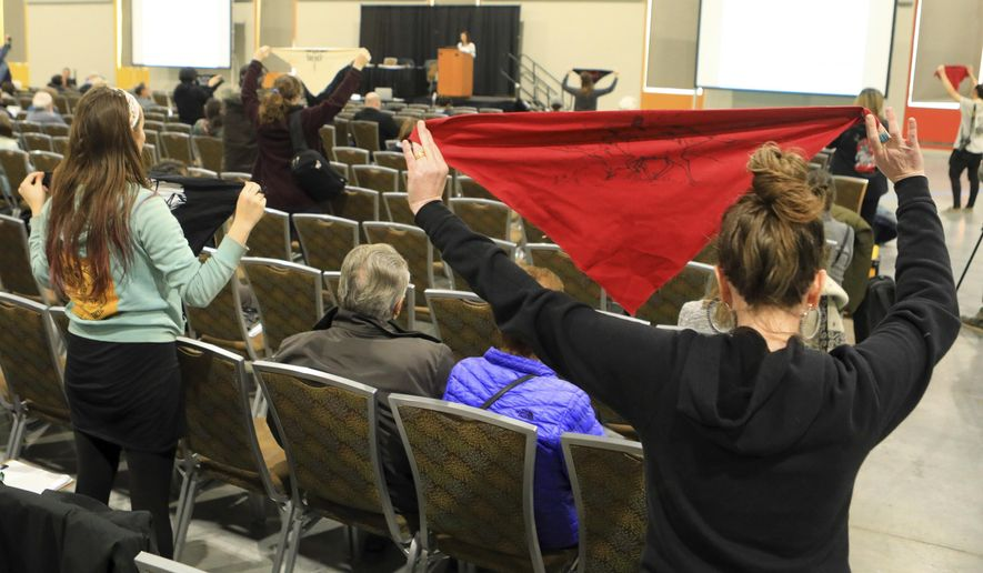 Protesters hold up flags during a public hearing on a draft environmental plan on proposed petroleum leasing within Alaska's Arctic National Wildlife Refuge on Monday, Feb. 11, 2019, in Anchorage, Alaska. Congress in December 2017 approved a tax bill that requires oil and gas lease sales in the refuge to raise revenue for a tax cut backed by President Donald Trump. (AP Photo/Dan Joling)
