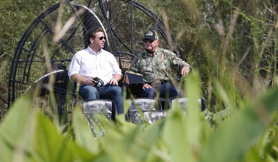 """FILE- In this Sept. 12, 2018 file photo, Republican candidate for Florida Governor Ron DeSantis, left, chats with Ron Bergeron during an airboat tour of the Florida Everglades, in Fort Lauderdale, Fla. Gov. Ron DeSantis appointed Ron """"Alligator Ron"""" Bergeron to the South Florida Water Management District board February 1, 2019, a position responsible for flood protection, Everglades restoration and water policy for 16 counties. (AP Photo/Wilfredo Lee, File)"""