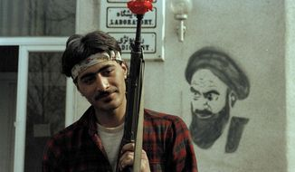 FILE - In this Feb. 15, 1979 file photo, a follower of Ayatollah Ruhollah Khomeini holds a rifle containing a flower outside of Khomeini's headquarters in Tehran, Iran. Monday, Feb. 11, 2019 marks the 40th anniversary of the Islamic Revolution in Iran, which overthrew the caretaker government left behind by the cancer-stricken Shah Mohammad Reza Pahlavi, who had left the country only weeks earlier. (AP Photo/Michel Lipchitz, File)