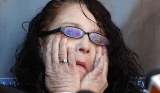 Anya Chapman wipes away tears as attorney Marc J. Victor speaks to the media concerning Chapman's husband, Johnny Wheatcroft, Monday, Feb. 11, 2019, in Chandler, Ariz. Victor has filed a lawsuit on behalf of Wheatcroft claiming the Glendale, Ariz. police dept. used excessive force against Wheatcroft during his arrest in 2017. (AP Photo/Matt York)