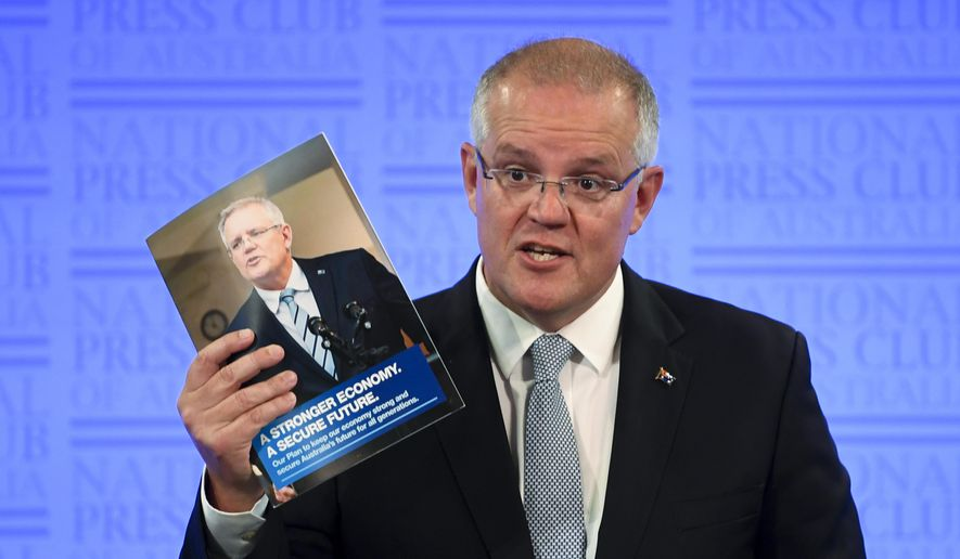 Australian Prime Minister Scott Morrison holds a booklet as he delivers an address to the National Press Club in Canberra, Monday, Feb. 11, 2019. Morrison used the speech on the eve of Parliament's first sitting day of the year to detail his conservative coalition's record on a diverse range of security issues including military spending, stripping extremists of Australian citizenship, asylum seekers, contentious laws to prevent criminals using encrypted communications and domestic violence. (Lukas Coch/AAP Image via AP)