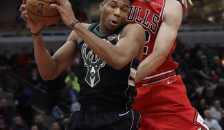 Milwaukee Bucks forward Giannis Antetokounmpo, left, rebounds a ball against Chicago Bulls center Robin Lopez during the first half of an NBA basketball game Monday, Feb. 11, 2019, in Chicago. (AP Photo/Nam Y. Huh)