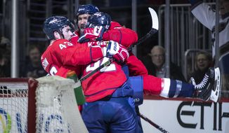 Washington Capitals center Evgeny Kuznetsov (92), of Russia, celebrates after scoring with right wing Tom Wilson (43) and left wing Alex Ovechkin (8), of Russia, during the second period of an NHL hockey game against the Los Angeles Kings, Monday, Feb. 11, 2019, in Washington. (AP Photo/Al Drago)