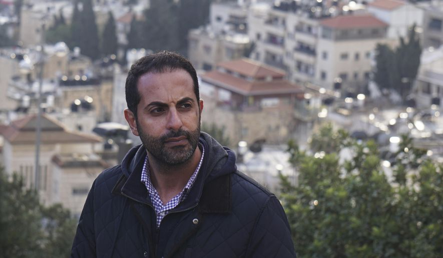 Lawyer Alaa Mahajna poses for a photo on Mount Scopus, overlooking Jerusalem, on Saturday, Feb. 9, 2019. Mahajna was one of at least half a dozen people targeted by a mysterious group of undercover operatives over the past couple of months. All of them have crossed paths, in some way, with the NSO Group, a spyware maker that Mahajna is suing in Israeli court. (AP Photo/Raphael Satter)