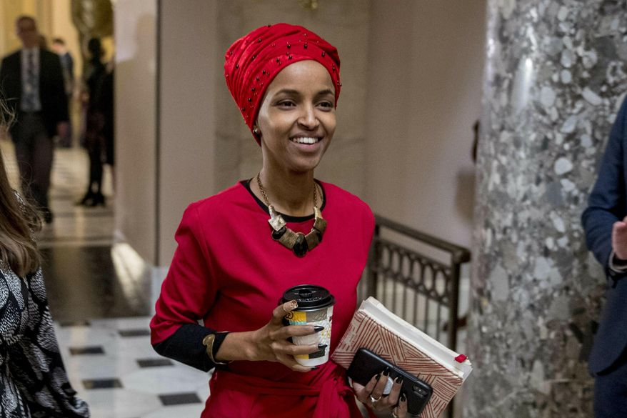 In this Jan. 16, 2019, file photo, Rep. Ilhan Omar, D-Minn., center, walks through the halls of the Capitol Building in Washington. (AP Photo/Andrew Harnik)