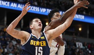 Denver Nuggets center Nikola Jokic, left, fights for control of a rebound with Miami Heat center Hassan Whiteside, right, in the first half of an NBA basketball game Monday, Feb. 11, 2019, in Denver. (AP Photo/David Zalubowski)