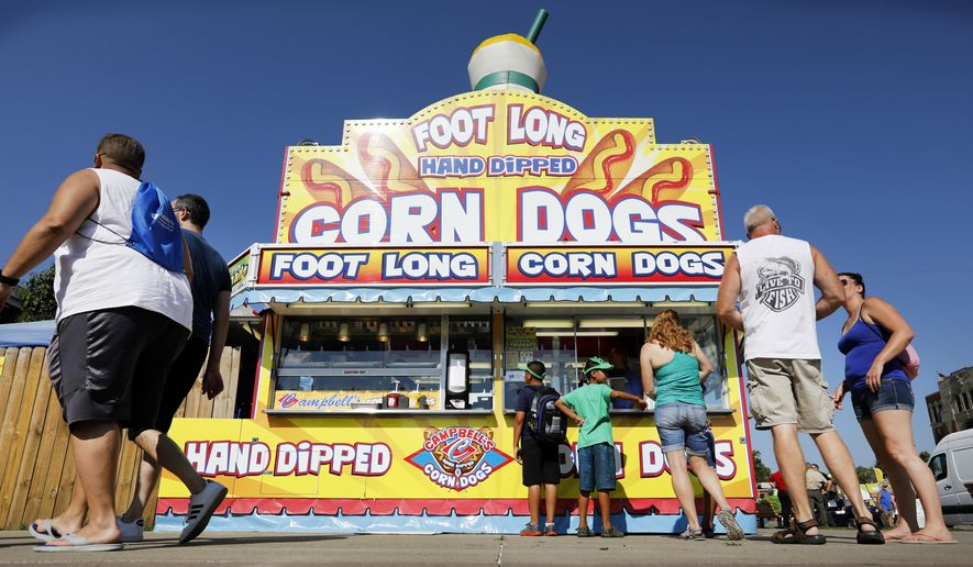 FILE - In this Aug. 9, 2018 file photo, Iowa State fairgoers line up to get a corn dog at a concession stand during the opening day of the Iowa State Fair in Des Moines, Iowa. The Iowa State Fair has confirmed that it will require all food and drink vendors to accept credit and debit card payments beginning in 2020. Cash has long been the dominant method of payment for the fried cheese curds, corn dogs, and scores of other foods bought by fairgoers. (AP Photo/Charlie Neibergall, File)