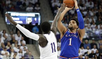 TCU forward Lat Mayen (11) defends as Kansas forward Dedric Lawson (1) attempts a shot in the first half of an NCAA college basketball game in Fort Worth, Texas, Monday, Feb. 11, 2019. (AP Photo/Tony Gutierrez)
