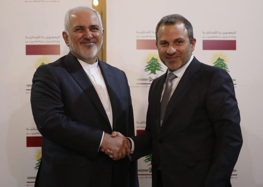 Lebanese Foreign Minister Gebran Bassil, right, shakes hands with his Iranian counterpart Mohammad Javad Zarif, in Beirut, Lebanon, Monday, Feb. 11, 2019. Zarif extended an offer for Iranian military assistance to the U.S.-backed Lebanese army on Sunday, saying Iran is ready to assist in all sectors should the Lebanese government want it. (AP Photo/Hussein Malla)