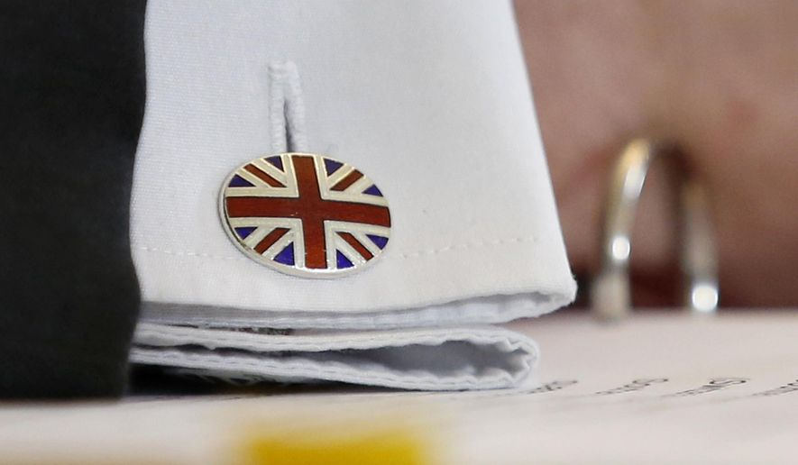A cuff button of British Secretary of State for International Trade Liam Fox shows the Union Jack, after signing a trade agreement with Swiss Federal Councillor Guy Parmelin (not pictured) in Bern, Switzerland, Monday, Feb. 11, 2019. Parmelin and Fox signed a bilateral trade agreement regulating relations between the two countries after the Brexit. Because of the customs treaty with Switzerland, the agreement also applies to Liechtenstein. (Peter Klaunzer/Keystone via AP)