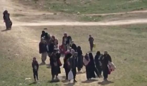 """In this Sunday, Feb. 10, 2019 image from video provided by Hawar News Agency, ANHA, an online Kurdish news service, civilians flee fighting near Baghouz, Syria. Fierce fighting was underway Monday between U.S.-backed Syrian forces and the Islamic State group around the extremists' last foothold in eastern Syria. The capture of the IS-held village of Baghouz and nearby areas would mark the end of a four-year global war to end IS' territorial hold over large parts of Syria and Iraq, where the group established its self-proclaimed """"caliphate"""" in 2014. (ANHA via AP) **FILE**"""