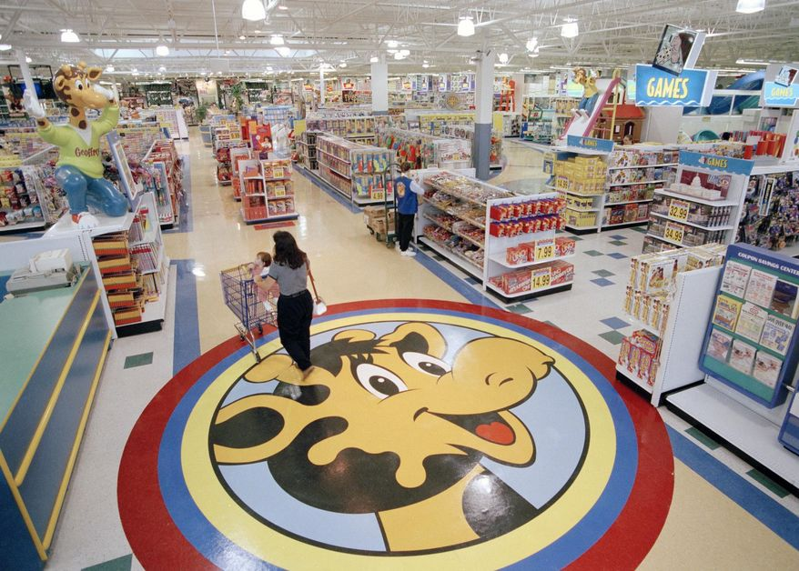 In this July 30, 1996, file photo, a woman pushes a shopping cart over a graphic of Toys R Us mascot Geoffrey the giraffe at the Toys R Us store in Raritan, N.J. Richard Barry, a former Toys R Us executive and now CEO of the new company called Tru Kids Inc., is exploring freestanding stores, shops within existing stores as well as e-commerce. Tru Kids, owned by former investors of Toys R Us, will manage the Toys R Us, Babies R Us and Geoffrey brands. (AP Photo/Daniel Hulshizer, File)
