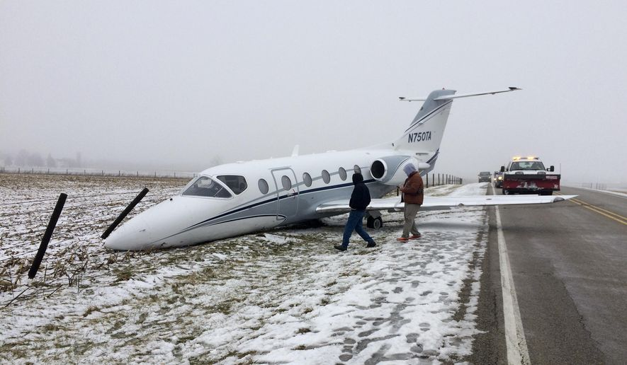 People look at a chartered plane at Richmond Municipal Airport on Monday, Feb. 11, 2019, in Richmond, Ind., that slid on a snowy runway. (Mike Emery/The Palladium-Item via AP)