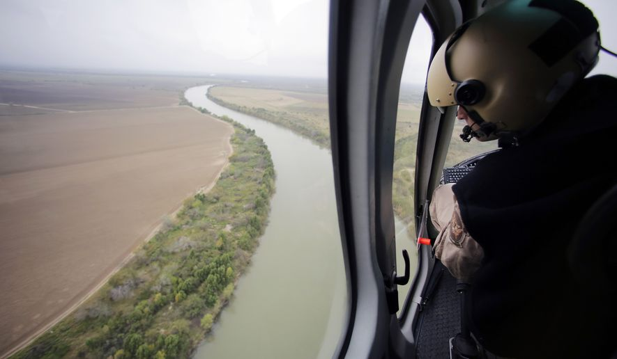 In this Tuesday, Feb. 24, 2015, aerial file photo, a U.S. Customs and Border Protection Air and Marine agent looks out along the Rio Grande on the Texas-Mexico border in Rio Grande City, Texas. (AP Photo/Eric Gay, File)