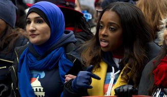 Co-presidents of the 2019 Women's March Linda Sarsour, left, and Tamika Mallory, center, march along with others demonstrators on Pennsylvania Av. during the Women's March in Washington on Saturday, Jan. 19, 2019. The Women's March returned to Washington on Saturday and found itself coping with an ideological split and an abbreviated route due to the government shutdown. (AP Photo/Jose Luis Magana)