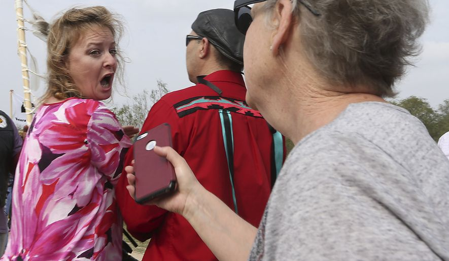Marianna Trevino-Wright, left, director of the National Butterfly Center, is confronted by a woman on the levee during a demonstration protesting the proposed border wall at the National Butterfly Center on Monday, Feb. 4, 2019 in Mission,Texas. (Delcia Lopez/The Monitor via Ap)/The Monitor via AP)