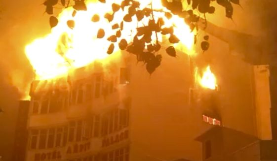 In this frame grab provided by Shyamal Duary, flames rise from a hotel that caught fire in the early hours of the morning in New Delhi, India, Tuesday, Feb. 12, 2019. A fire engulfed a shoddily built budget hotel in central New Delhi early Tuesday, killing 17 people and injuring at least four others, including a woman from Myanmar who leaped from an upper floor to escape the flames, Indian authorities said. (UGC Photo via AP)