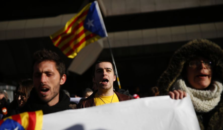 Pro independence demonstrators gather outside the Spanish Supreme Court in Madrid, Tuesday, Feb. 12, 2019. Spain is bracing for the nation's most sensitive trial in four decades of democracy this week, with a dozen Catalan separatists facing charges including rebellion over a failed secession bid in 2017. (AP Photo/Andrea Comas)