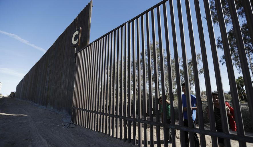 FILE - In this March 5, 2018, file photo, boys look through an older section of the border structure from Mexicali, Mexico, alongside a newly-constructed, taller section, left, in Calexico, Calif. A federal appeals court has rejected arguments by the state of California and environmental groups who tried to block reconstruction of sections of the U.S.-Mexico border wall. The 9th U.S. Circuit Court of Appeals ruled Monday, Feb. 11, 2019, that the Trump administration did not exceed its authority by waiving environmental regulations to rebuild sections of wall near San Diego and Calexico. (AP Photo/Gregory Bull, File)