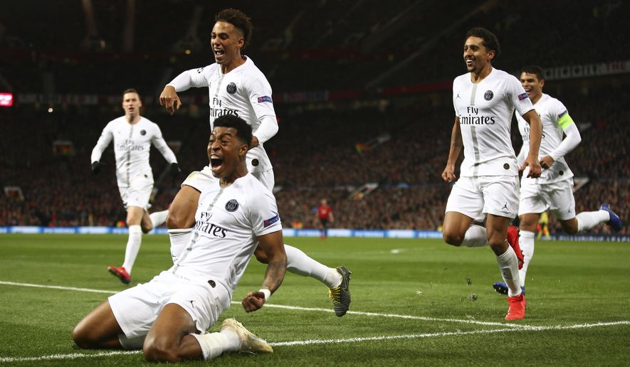 Paris Saint Germain's Presnel Kimpembe, left, celebrates after scoring the opening goal the game during the Champions League round of 16 soccer match between Manchester United and Paris Saint Germain at Old Trafford stadium in Manchester, England, Tuesday, Feb. 12,2019.(AP Photo/Dave Thompson)