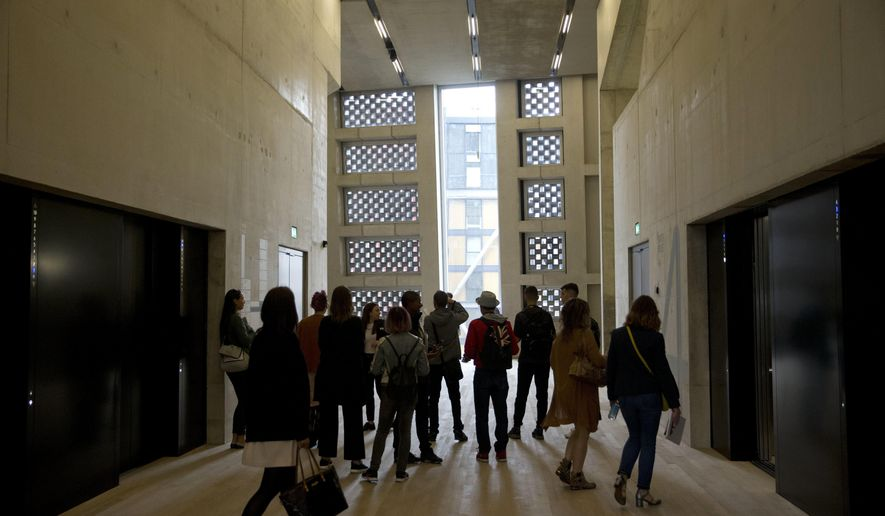 FILE - In this Tuesday, June 14, 2016 file photo, people stand in an area by the lifts in the new Switch House building extension to the Tate Modern gallery in London. On Tuesday Feb. 12, 2019, neighbors of London's Tate Modern lost a legal fight to force the art gallery to close a viewing platform that gives visitors a view into their homes.  (AP Photo/Matt Dunham, file)