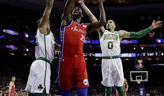 Philadelphia 76ers' Joel Embiid, center, goes up for a shot between Boston Celtics' Al Horford, left, and Jayson Tatum during the first half of an NBA basketball game, Tuesday, Feb. 12, 2019, in Philadelphia. (AP Photo/Matt Slocum)