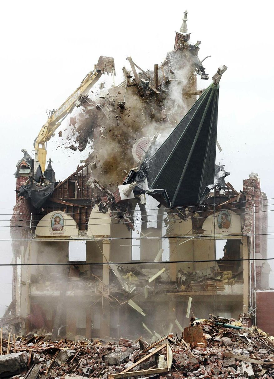 In this Monday, Feb. 11, 2019 photo, the steeple of Saint Joseph's Church in Nanticoke, Pa., is knocked down as Brdaric Excavating began the demolition of the property. The church and an adjoining rectory closed in May 2010 as part of the Catholic church consolidation. (Warren Ruda/The Citizens' Voice via AP)