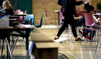 A teacher moves from table-to-table while teaching one of two combined sixth-grade classes in the gymnasium at Skinner Middle School during the first day of the Denver Public Schools teachers strike, Monday, Feb. 11, 2019, in Denver. More negotiations are set for Tuesday. (Joe Amon/The Denver Post via AP)