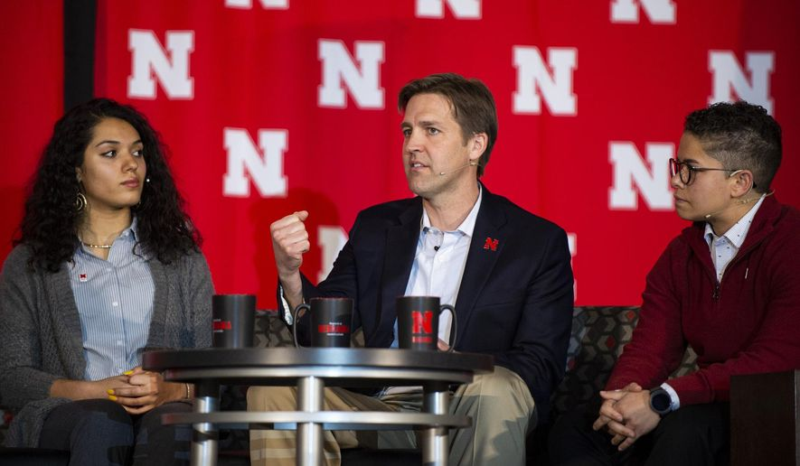 """In this Monday, Feb. 11, 2019 photo, U.S. Ben Sasse, R-Neb., answers a question posed to him during a panel discussion for the University of Nebraska's Charter Week Celebration while students Grace Chambers, left, and Kamryn Sannicks listen in Lincoln, Neb. Sasse said technology has undermined traditional community structures, and ideology or """"political tribes"""" are rushing to fill the void. He said political parties aren't adequate replacements for communities. (Savannah Blake/Lincoln Journal Star via AP)"""
