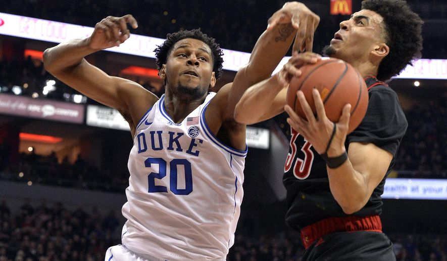 Duke center Marques Bolden (20) and Louisville forward Jordan Nwora (33) vie for a rebound during the first half of an NCAA college basketball game in Louisville, Ky., Tuesday, Feb. 12, 2019. (AP Photo/Timothy D. Easley)