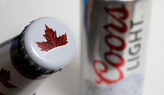 FILE- In this Nov. 28, 2017, file photo products from the Mondelez International family of brands, Molson beer, left, and Coors Light beer rest together, in Walpole, Mass. The Molson Coors Brewing Company reports financial results Tuesday, Feb. 12, 2019. (AP Photo/Steven Senne, File)