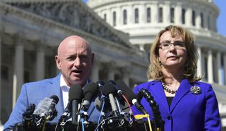 In this Oct. 2, 2017, file photo former Rep. Gabrielle Giffords, D-Ariz., right, listens as her husband Mark Kelly, left, speaks on Capitol Hill in Washington. Kelly said Tuesday, Feb. 12, 2019, that he's running to finish John McCain's term in the U.S. Senate. (AP Photo/Susan Walsh, File)