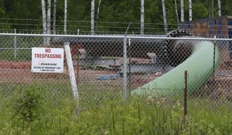 FILE - In this June 29, 2018 file photo, a No Trespassing sign is visible at a Enbridge Energy pipeline drilling pad along a rail line that traces the Minnesota-Wisconsin border south of Jay Cooke State Park in Minnesota. Gov. Tim Walz says his administration will continue to appeal a regulatory commission's approval of Enbridge Energy's plan to replace its aging Line 3 crude oil pipeline. The commission approved the project last summer, but former Gov. Mark Dayton's Department of Commerce appealed that decision, as did several environmental and tribal groups. An appeals court decision last week sent the challenges back to the commission for further proceedings. (AP Photo/Jim Mone)