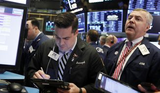 FILE- In this Feb. 5, 2019, file photo traders Joseph Lawler, left, and James Lamb work on the floor of the New York Stock Exchange. The U.S. stock market opens at 9:30 a.m. EST on Tuesday, Feb. 12. (AP Photo/Richard Drew, File)