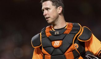 FILE - In this Aug. 24, 2018, file photo, San Francisco Giants catcher Buster Posey talks to an umpire during the sixth inning of a baseball game against the Texas Rangers, in San Francisco. Working out his lower body with a 15-pound dumbbell in his left hand he leaned forward to do a one-legged dead lift. Posey immediately felt the muscles in his right buttocks being used exactly the way they should. Posey certainly plans to be a full participant from Day 1 of spring training, pulling on the catcher's gear and squatting behind the plate for bullpens. (AP Photo/John Hefti, File)