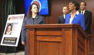 Prosecutor Ryann Jorban, left, who's on the immigrant fraud unit stands and looks on as District Attorney Jackie Lacey announces prosecutions during a news conference on Tuesday, Feb. 12, 2019 in Los Angeles. Operating with virtual impunity in Los Angeles for years, con artists have long targeted immigrants desperate for help to become U.S. citizens and other expert legal help, defrauding them of life savings and only hastening their deportation or other disasters. But a new fraud unit at the district attorney's office has been targeting the fraudsters since 2017, prosecuting eight cases that cheated at least 300 immigrants out of at least $3 million, prosecutors announced Tuesday. (AP Photo/Amanda Lee Myers)