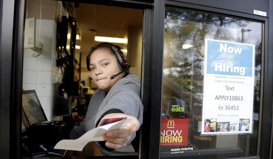 FILE- In this Jan. 3, 2019, file photo a cashier returns a credit card and a receipt at a McDonald's window, where signage for job openings are displayed in Atlantic Highlands, N.J. On Tuesday, Feb. 12, the Labor Department reports on job openings and labor turnover for December. (AP Photo/Julio Cortez, File)